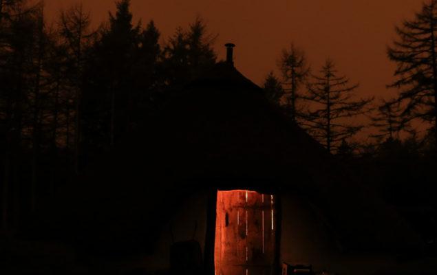 Ett hus med öppen dörr i mörker.
