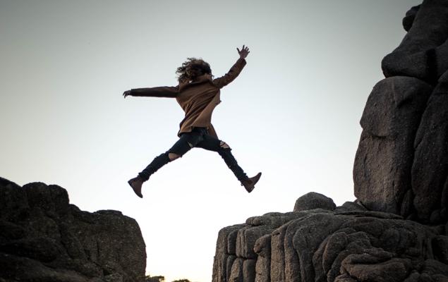 Person som hoppar från klippa till klippa.