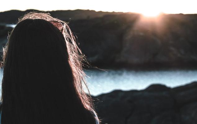 Flicka och solnedgång vid vatten.