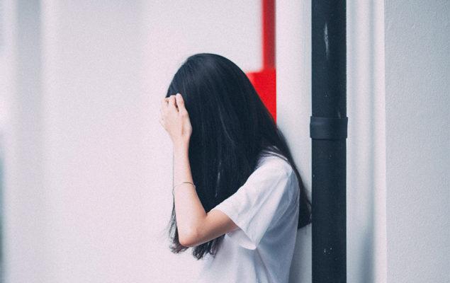 En flicka står mot en vägg.