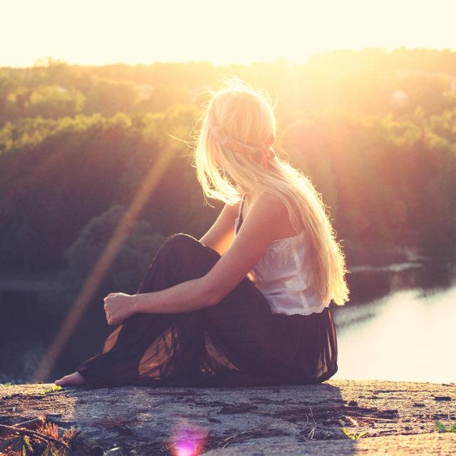Flicka som sitter i solsken.
