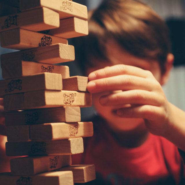 En pojke bygger med klossar.